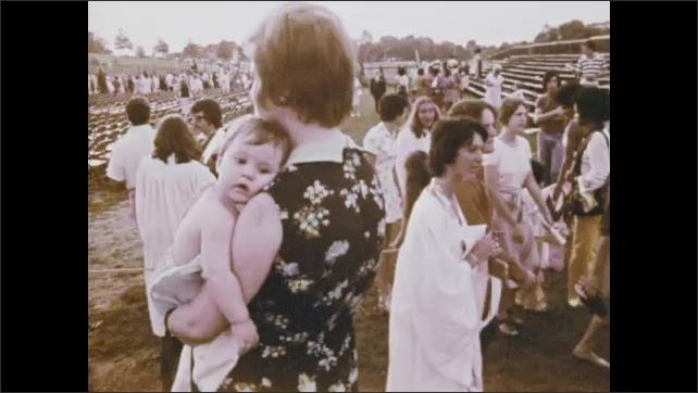 1970s: Man talking. Pan of graduation ceremony. Man talking. People pose for photo. Man talking. Woman talking. Woman with baby. Woman talking. Views of graduation ceremony.