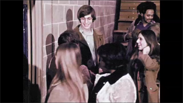 1970s: Students gather at exit to gymnasium after assembly. Student talks to group.