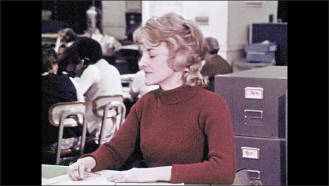 1970s: Two young men talking. Woman talks, gets up and answers phone in office. Woman talks on phone in office.