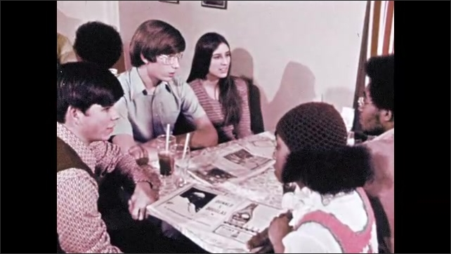 1970s: Newspaper. Young man holds newspaper sitting at table with other people, talking. Two people enter building with sign saying: Polling Place.
