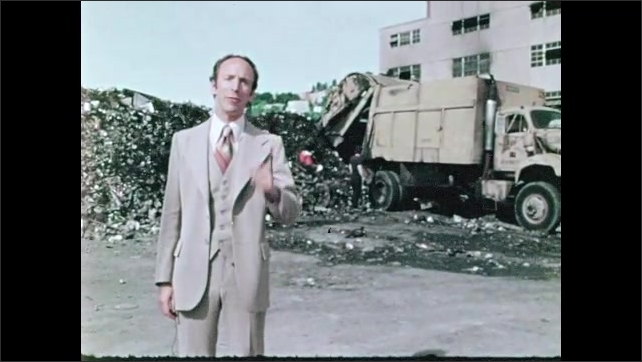 1970s: church steeple and tree branches, man in suit at garbage dump talks and points as garbage truck dumps garbage behind him, man walks off