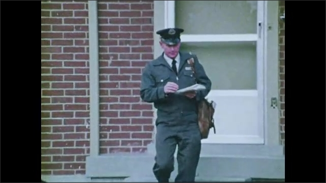 1970s: Mailman walks up to house, delivers mail. Mailman walks across lawn, waves at people standing in doorway. Man and woman stand in doorway, talk.