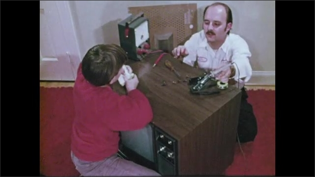 1970s: Garbage men load garbage into truck. Plumber fixes sink. Boy eats sandwich, watches man repair television. Man repairs telephone. Boy delivers newspapers.