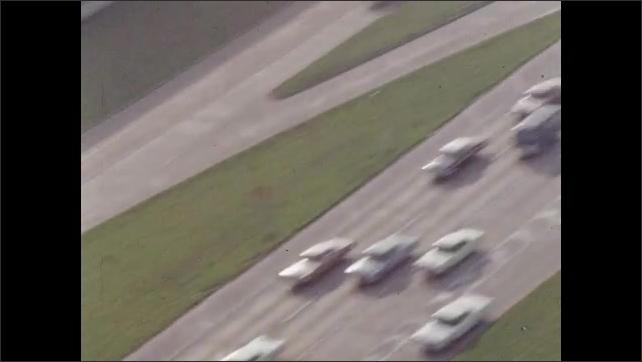 1960s: Cars travel on freeway. Steel beams strewn across side of freeway.