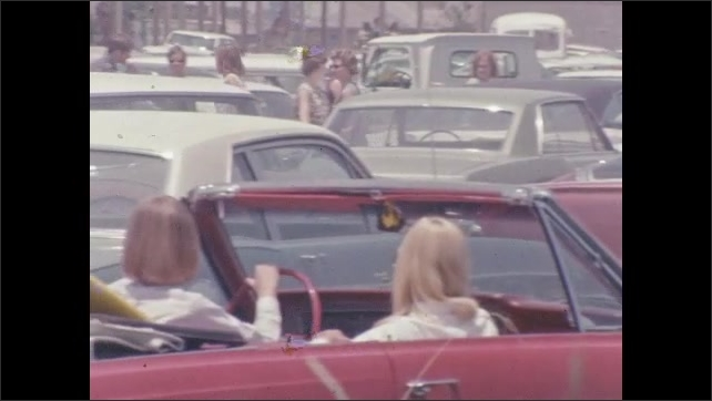 1960s: Cars in parking lot. Convertible car with surfboard in back. Woman in driver seat looks around.