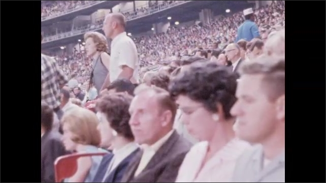 1960s: People in stands at sports game. Side view of crowd in arena. High angle view of crowd.