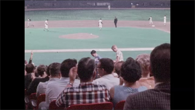1960s: High angle view of crowd in stands at baseball game, player at bat. Players on field, crowd applauding. Side view of crowd. High angle view of game, women walk up steps.