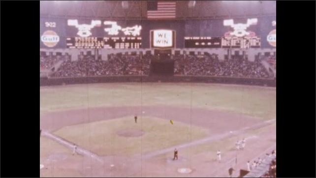 1960s: High angle view of baseball game, hand covers camera lens. High angle view of game, lights on scoreboard.