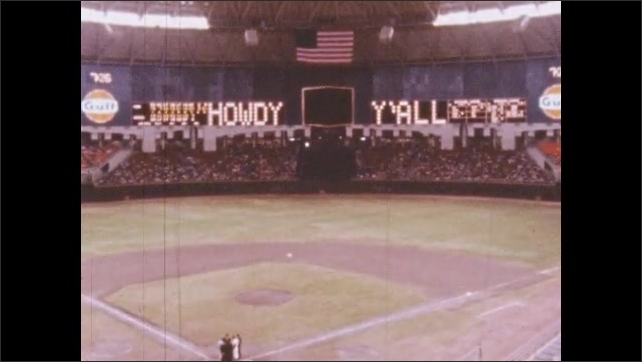 1960s: Interior of baseball stadium, zoom out from scoreboard.
