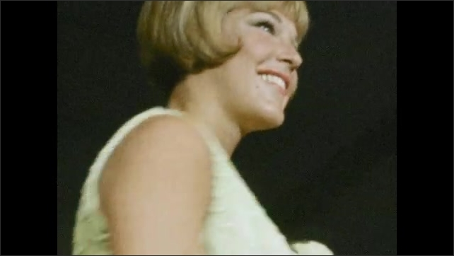 1960s: Low angle, woman turning on runway. Woman turning. Tilt up woman on runway. Women pass on stage.