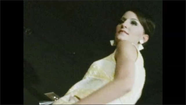 1960s: Close up of woman, tilt down, woman walking on runway. Woman on stage. Low angle, woman walking. Low angle of woman. Woman walking. Low angle of woman.