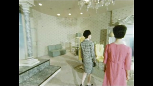 1960s: Mannequins on stage, pan to women shopping. Mannequins on stage, pan to women shopping, zoom in. Interior of store, woman walks past rack.
