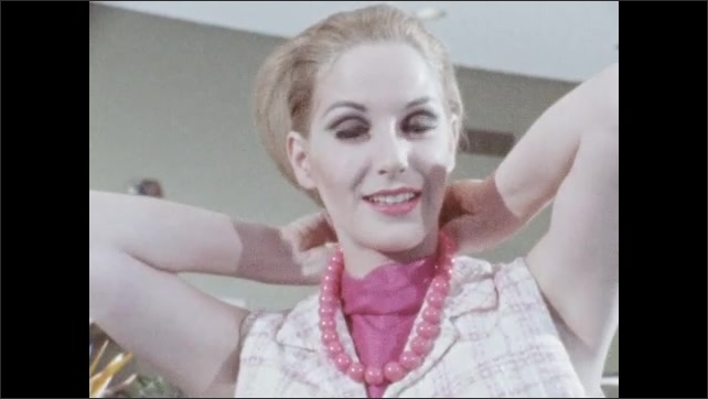 1960s: Close up of woman's face, zoom out, woman puts on necklace, zoom in on necklace.