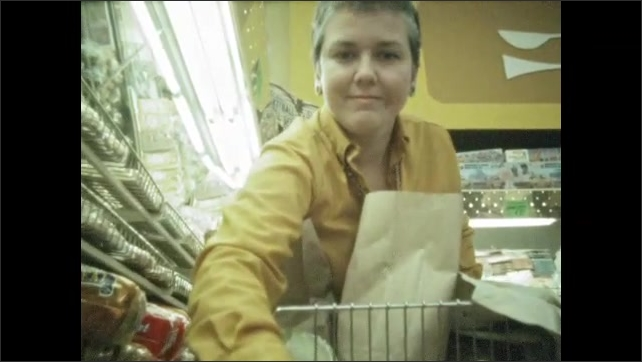 1960s: Low angle, woman in store, puts bread in cart. Shots of woman putting bread in cart.