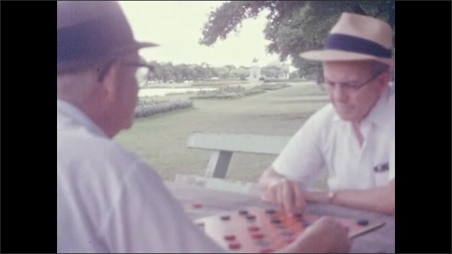 1960s: Men play checkers in park.  Cars drive down street.