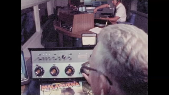 1960s: Record on player spins as men sit at audio control panels in studio. Man holds record sleeve over record player.