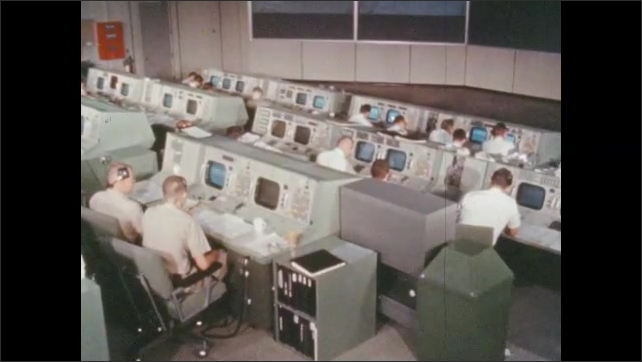 1960s: People sitting at rows of consoles in NASA mission control room.