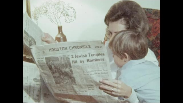 1970s: UNITED STATES: lady reads newspaper. Boy looks at paper with lady. Close up of boy and lady