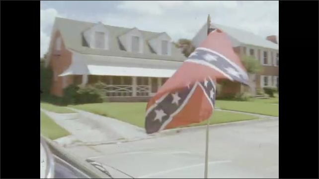 1970s: UNITED STATES: car with flag. Stars and stripes flag.