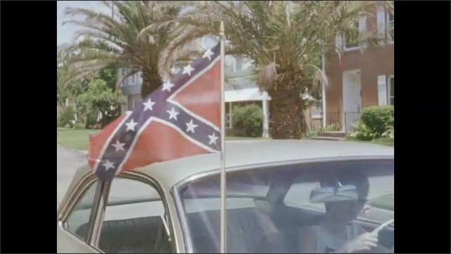 1970s: UNITED STATES: flag attached to car. Flag blows in breeze.