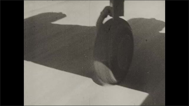 1940s: Soldiers by plane. Soldiers kneeling. Soldiers climb into plane. Plane moving on runway. Close up, wheel of plane lifting. Pan of plane flying.