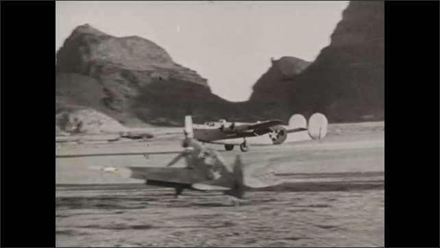 1940s: Aerial view of mountains. Plane landing on runway. View of sign. Planes on runway, men driving transport vehicle.