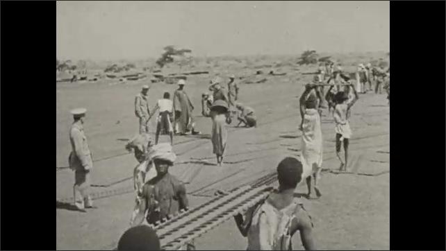 1940s: Men working in field, plane flies over. Men digging in soil. Men carrying equipment. Men set down metal slabs. Hnads connecting metal slabs.