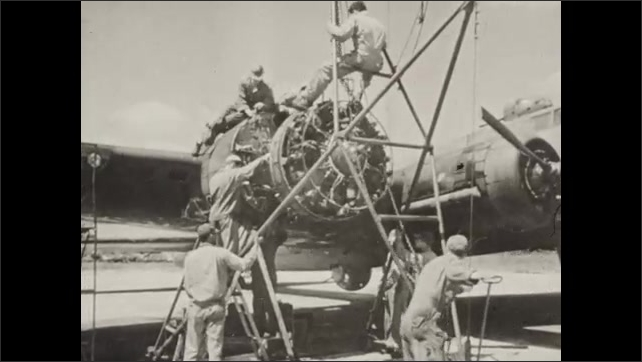 1940s: Hands laying down metal slabs. Men cleaning parts on ceiling. Men attach engine part to plane. Men working on plane. People walk through revolving door. People looking at exhibit.