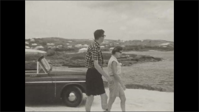 1950s: Couple get out of a car with a surfboard on top and walk on the beach.