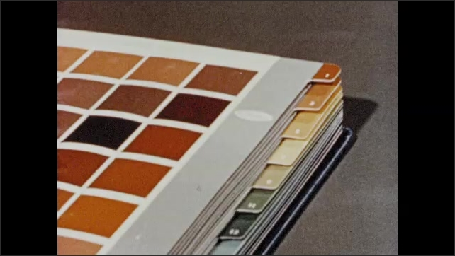 1950s: Woman runs finger down dividers in book of color samples. Woman begins turning pages of book.