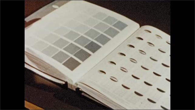 1950s: Woman compares drapes to color wheel then points at colors on wheel. Woman opens book of color pallets. Woman takes strip of colors from book.