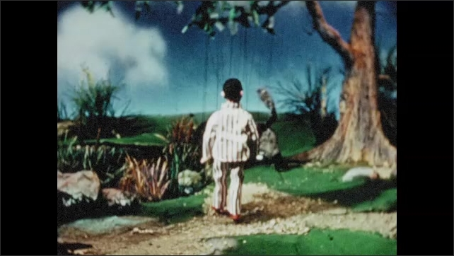 1950s: UNITED STATES: dog and boy walk under tree. Dog wags tail. Puppet dog drinks water from river.