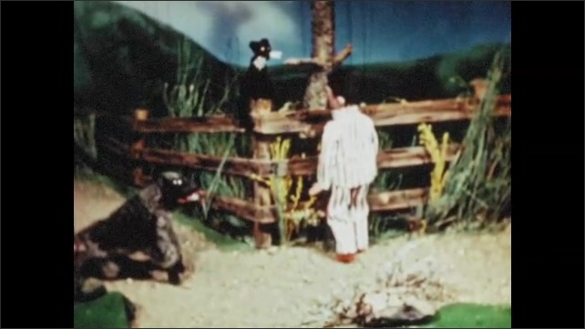 1950s: UNITED STATES: cat sat on fence. Boy and dog talk to cat on fence. Boy talks to cat.