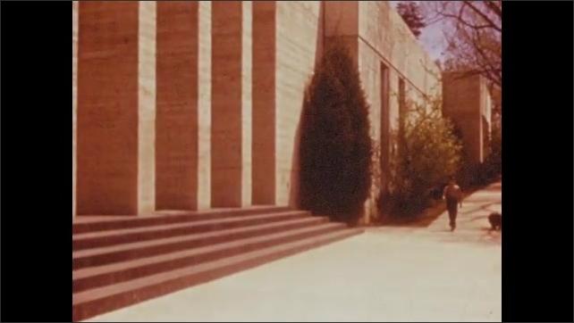 1950s: UNITED STATES: boy wakes up. Boy walks along sidewalk past building. Boy and dog walk up steps. Dog waits by door.