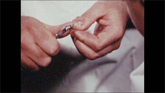 1950s: UNITED STATES: dentist puts grinder together. Dentist drills on finger nail. Dentist drills on boy's finger nail.