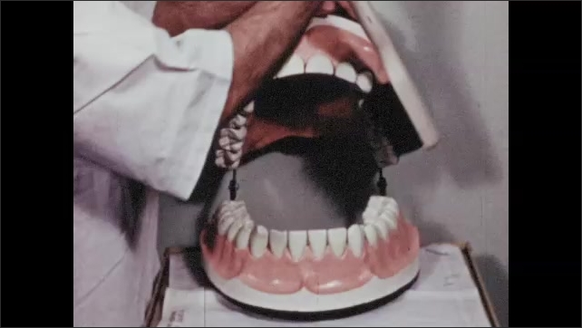 1950s: UNITED STATES: dentist uses rotary motion to brush surface of teeth. Dentist changes angle of toothbrush.