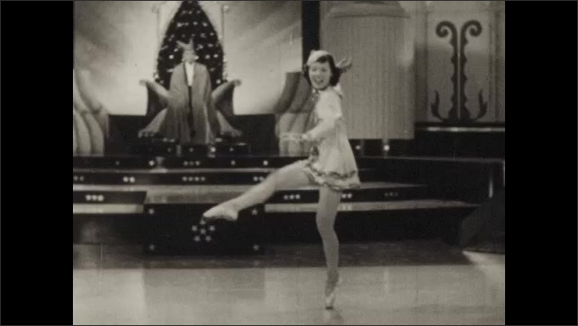 1940s: UNITED STATES: lady takes off cloak and dances for man on stage. Lady spins on spot. Lady in ballet shoes dances on points.