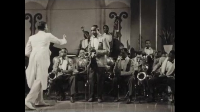 1940s: UNITED STATES: man reads from parchment. Man nods at band. Man dressed as devil on throne. Man conducts band