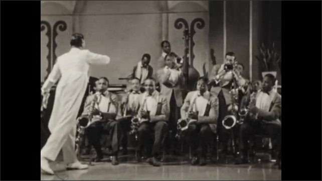 1940s: UNITED STATES: man plays saxophone. Man conducts jazz band. Man stands and plays instrument