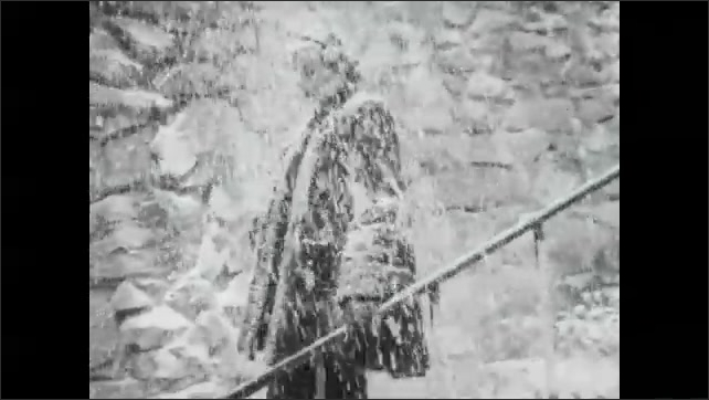 1930s: Women stand outside in fur coats. Man throws snow on women. Men push snow off ledge onto women.