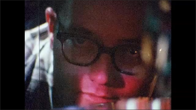 1930s: UNITED STATES: hand feeds card into computer system. Close up of man's face by computer lights. Close up of computer buttons
