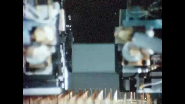 1930s: UNITED STATES: close up of factory machines at work. Computer controlled machines. Wire wrapping technique