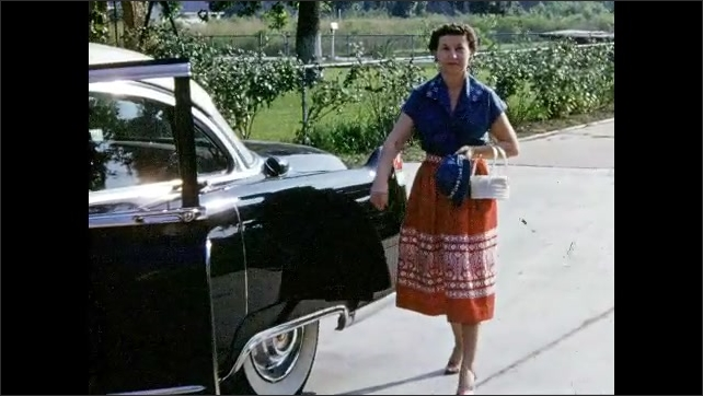 1950s: Man stands next to car, waves. Woman walks around back of car, enters car, sits down in driver seat.