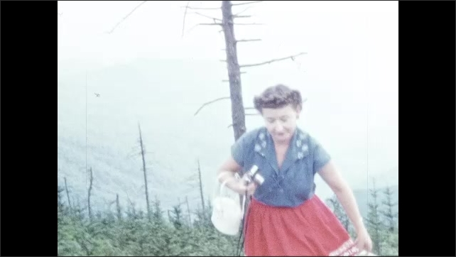 1950s: Sign for Gatlinburg, TN. Woman sits on rock in front of mountains, holds camera. Woman stands and looks at mountains.