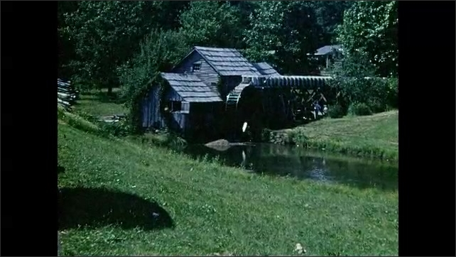 1950s: Water wheel spins at old mill.