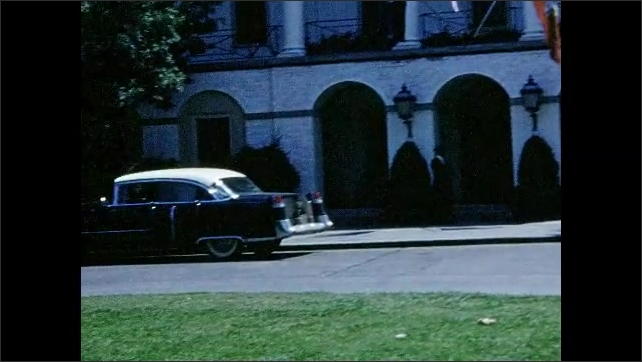 1950s: Cars parked in front of large building. Historical marker and monument.