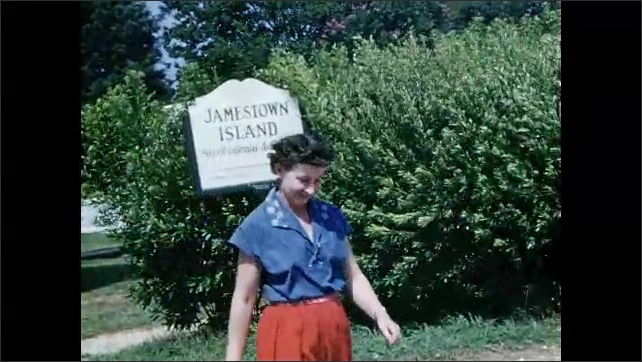 1950s: Woman walks over and stands next to historical marker. Large colonial style busiling.