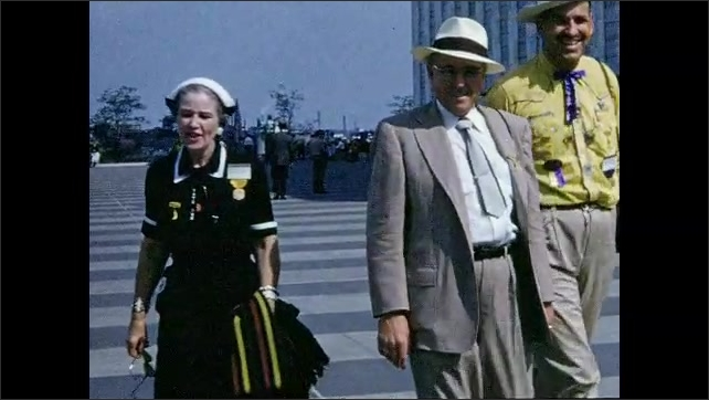 1950s: Woman and men walk on street in front of United Nations building.