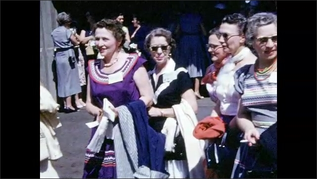 1950s: Women stand in large crowd, smile and talk.