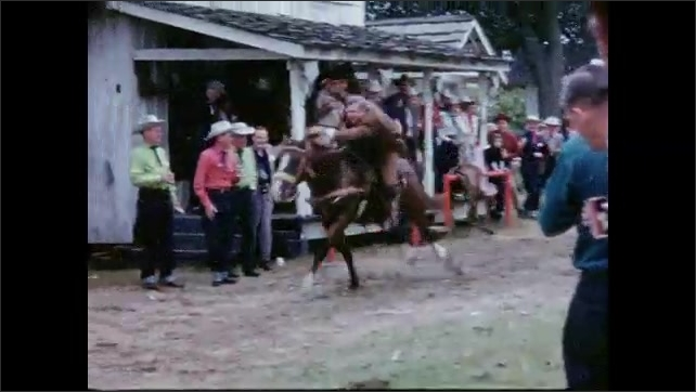 1950s: UNITED STATES: man rides horse at fair. Ladies in period costume. Cowboy chases Indian on horseback.
